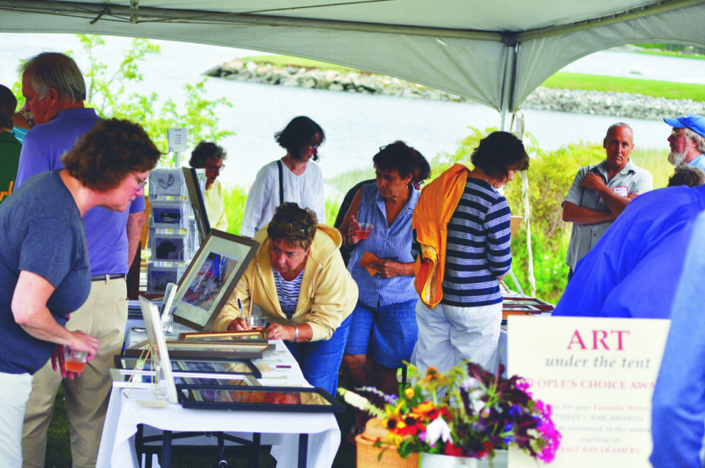 """Community members peruse art on display and fill out ballots for the People's Choice Award during a previous Lobster and More event, with the """"Art Under the Tent,"""" held at the Lincoln Home in Newcastle."""