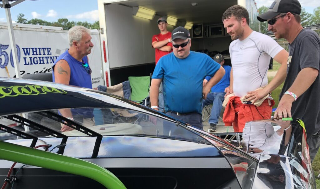 Ben Ashline, second from right, and car owner Ajay Picard, far right, look over their No. 99 during practice for a Pro All Stars Series race at Oxford Plains Speedway in July.