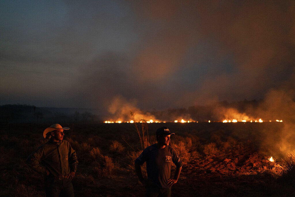 Neri dos Santos Silva, center, watches an encroaching fire threat after digging trenches to keep the flames from spreading to the farm he works on, in the state of Mato Grosso, Brazil, on Friday. Associated Press/Leo Correa