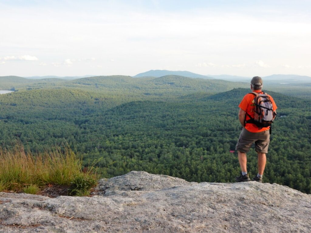 Carey Kish takes in the view of Pleasant Mountain from atop the sweeping cliffs on Sabattus Mountain.