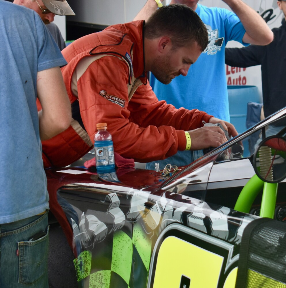Pittston's Ben Ashline works on his car during a break in practice runs for the Oxford 250 last Saturday at Oxford Plains Speedway in Oxford.