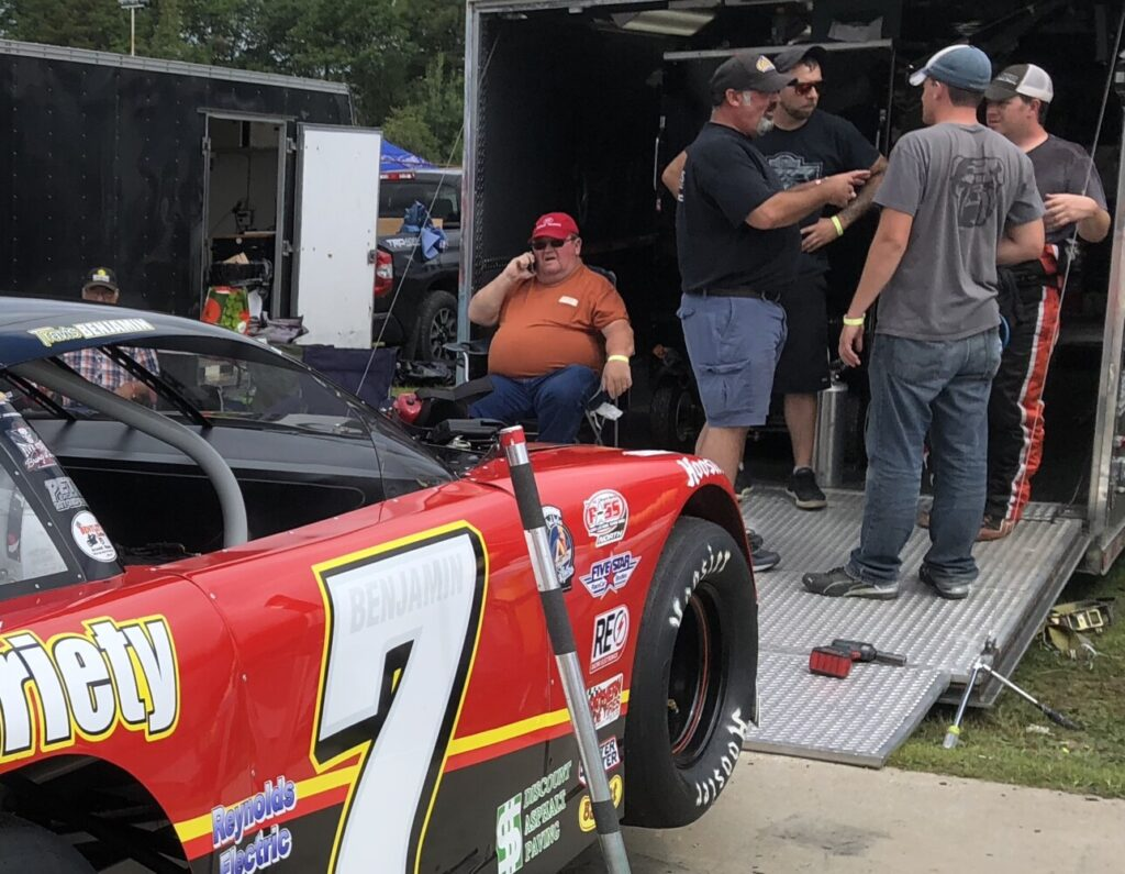 Ron Benjamin, seated left, and Travis Benjamin, far right, over see their team's pit area during practice Saturday for the 46th annual Oxford 250 at Oxford Plains Speedway.