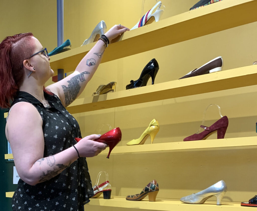 "Emma Sieh, collections and exhibits coordinator at Museum L-A, looks over shoes that are part of its current footwear exhibit. Some of the shoes will be used in its upcoming ""The Shoe Must Go On"" shoe fashion show being held Friday, Sept. 20, at the Lewiston museum. Community members willing to model shoes in the shoe fashion show, as well as lend their own shoes, are being sought. Deadline for submission forms is Aug. 20."