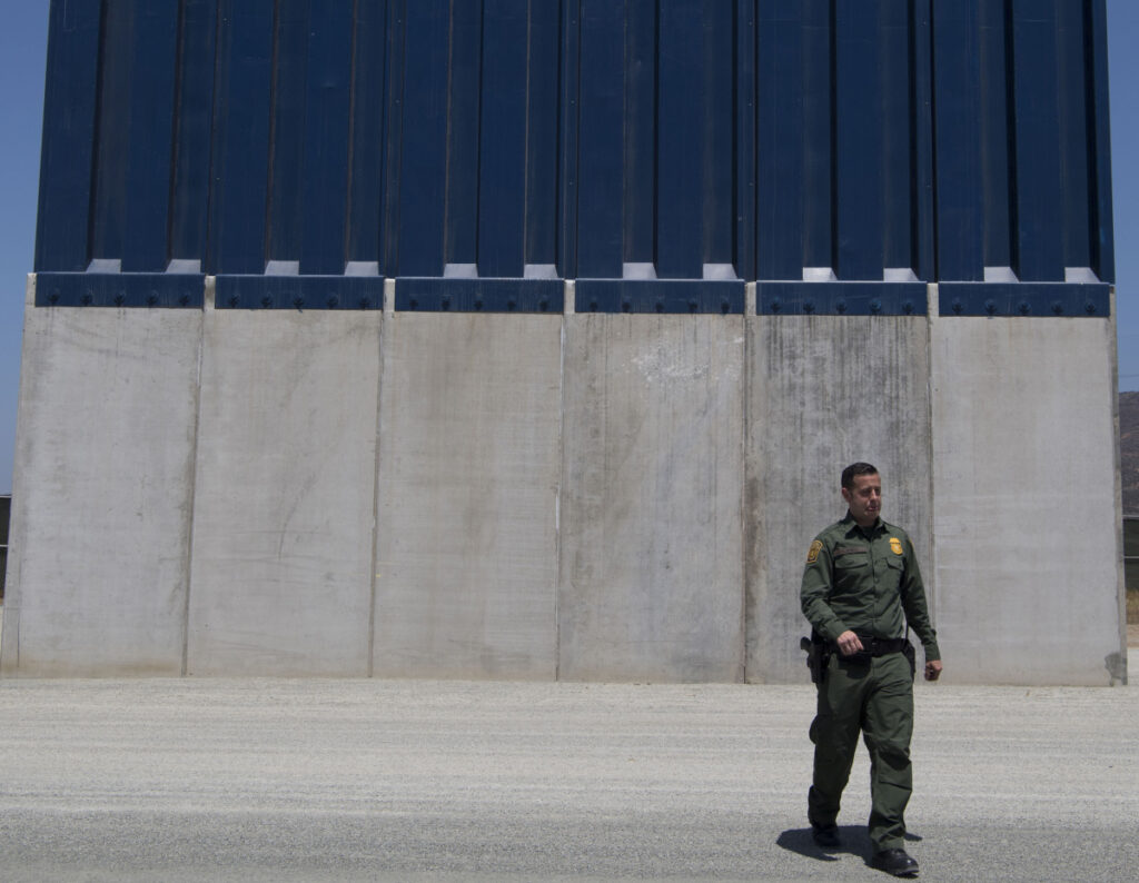 A Border Patrol official inspects border wall prototypes in the San Diego area in April 2018.