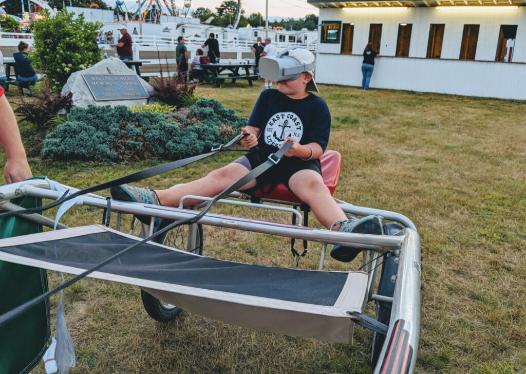 A young fan tries the Maine Harness Horseman's Association's new virtual reality simulator at the Skowhegan State Fair in Skowhegan this week.