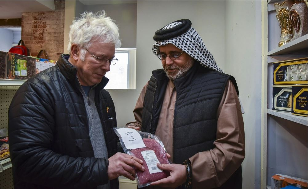 Central Maine Meats co-owner Joel Davis, left, discusses distribution of halal-certified meat with Khalid Zamat, owner of a newly opened Iraqi grocery store in Hallowell, in 2017.