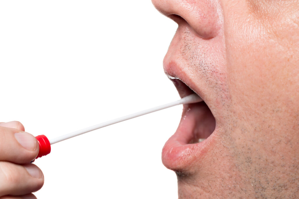 A man takes a DNA test, using a cotton swab. When food writer Meredith Goad took the test, she used the spitting collection method. The results tell her, in part, why she likes, and doesn't like, certain foods.