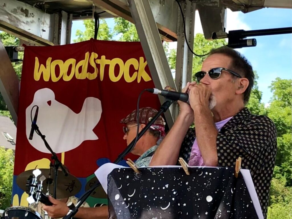 Jay Conway of the band Canned Heat plays the harmonica Sunday during Hallowell's Woodstock and Art Festival.