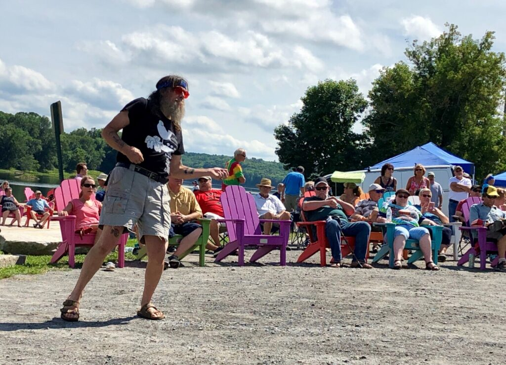 Zoo Cain strums an air guitar Sunday during Hallowell's Woodstock and Art Festival. Cain said he hitchhiked from Boston to the festival 50 years ago.