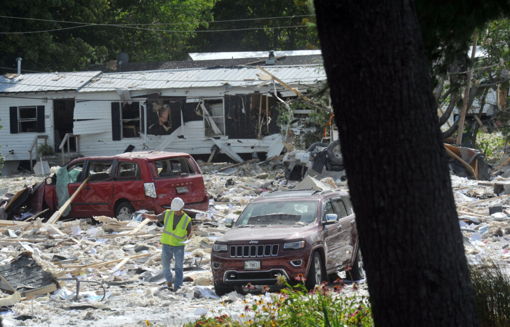 Building material and other debris is shown following a building explosion in Farmington on Monday. The explosion also damaged nearby mobile homes, in background.