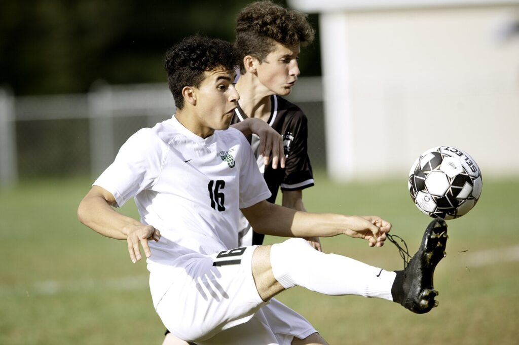 Pat Shaw, left, of Waynflete tries to win the ball against Thomas Suckow of St. Dominic Academy during the first half in Auburn on Tuesday. Waynflete won the game, 3-0.