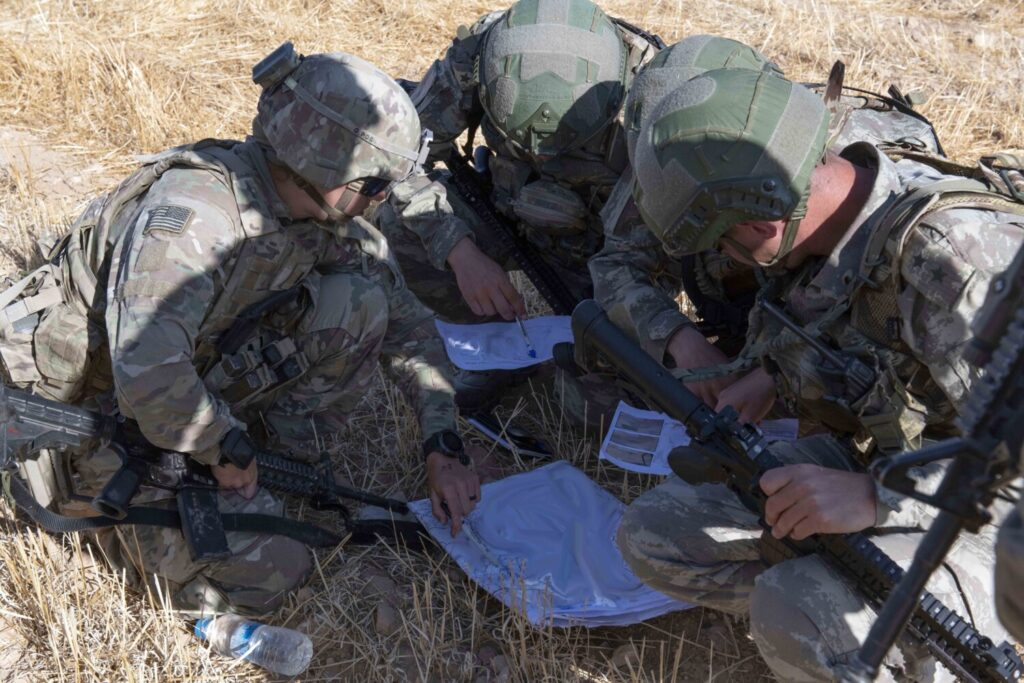 "U.S. and Turkish military forces go over a map last month in preparation for their second joint ground patrol inside the so-called ""safe zone"" in northeast Syria near the border with Turkey."