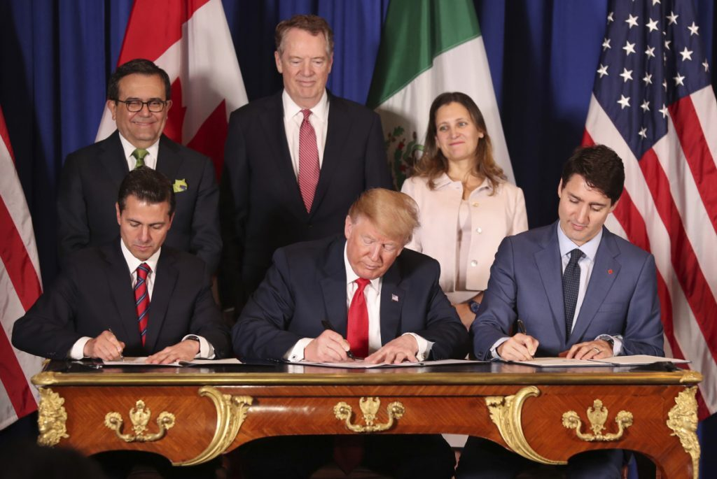 President Trump sits between Canada's Prime Minister Justin Trudeau, right, and Mexico's President Enrique Pena Nieto as they sign the United States-Mexico-Canada Agreement, which is replacing the NAFTA trade deal, during a ceremony Friday at a hotel before the start of the G20 summit in Buenos Aires, Argentina. The USMCA, as Trump refers to it, still needs approval by lawmakers in all three countries.