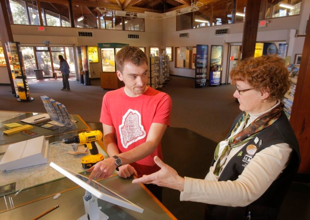Nate Wildes of Live + Work in Maine explains the operation of an iPad kiosk to Marcia Peverly, manager of the Maine State Visitor Information Center in Kittery, in 2016.   Live + Work is partnering with Educate Maine in an effort to keep college graduates in Maine.
