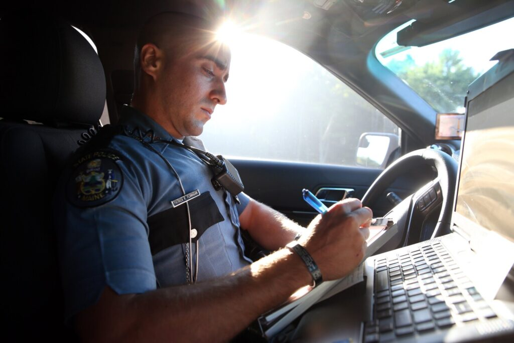 Maine State Trooper Pat Flanagan writes a ticket for a truck driver who was following Flanagan's unmarked cruiser too closely on Interstate 95 on Thursday during a distracted driver detail.
