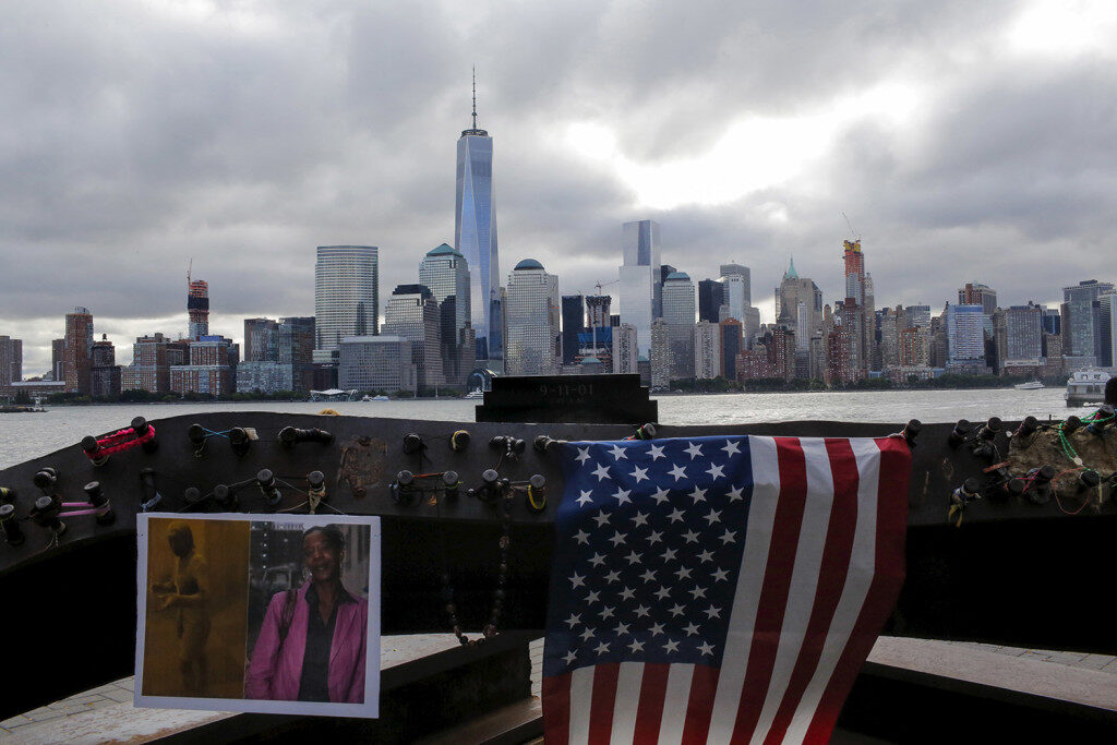 Souvenirs for 9/11 victims are seen in a memorial across from New York's Lower Manhattan and One World Trade Center in Exchange Place, New Jersey September 11, 2015. An overcast Friday greeted relatives who gathered to commemorate nearly 3,000 people killed in the September 11 attacks in New York, Pennsylvania and outside Washington 14 years ago, when airliners hijacked by al Qaeda militants brought death, mayhem and destruction. REUTERS/Eduardo Munoz - RTSNF1