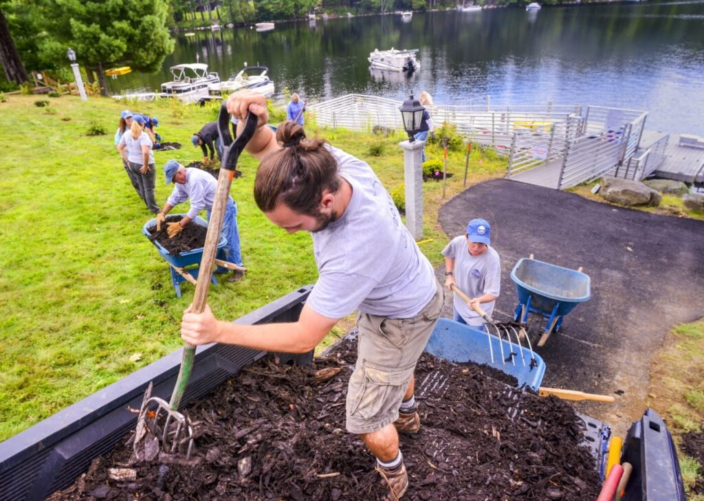 Jacob Violette, center, scoops erosion control mulch from a pickup truck on Tuesday at the waterfront area of Travis Mills Foundation retreat on Long Pond in Rome.