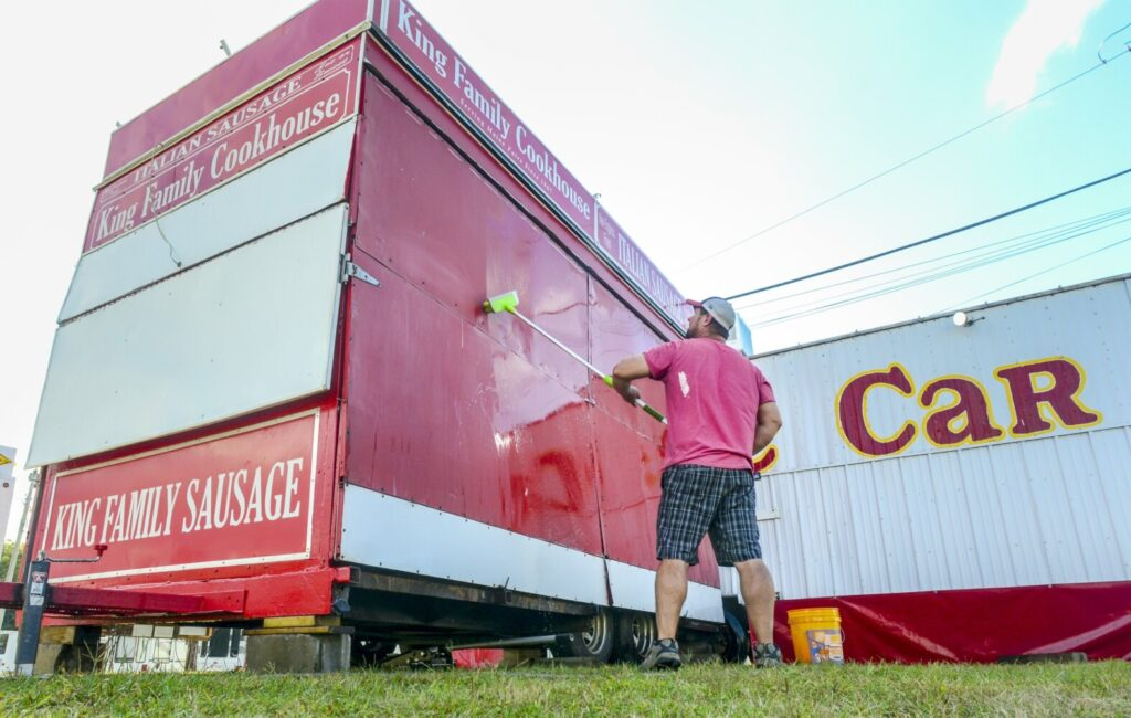 Jared Goodwin scrubs down the King Family Cookhouse trailer Tuesday at the Litchfield Fairgrounds. He'd just moved the family's summer business from the Windsor Fair where they'd worked the previous week.