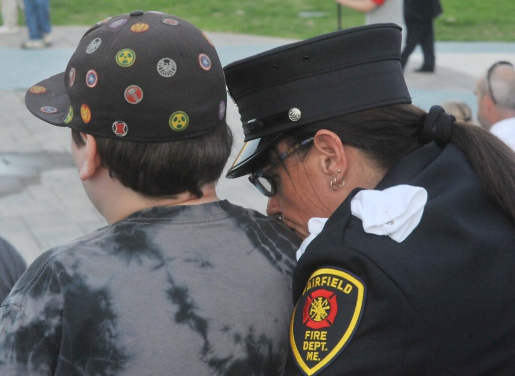 Stephanie Aucoin, of the Fairfield Fire Department, shares a quiet moment with her grandson Damian Colby, 11, during a ceremony commemorating the 18th anniversary of the Sept. 11, 2001, terrorist attacks. Wednesday's ceremony, which drew about 50 people, was held along the RiverWalk in Waterville.