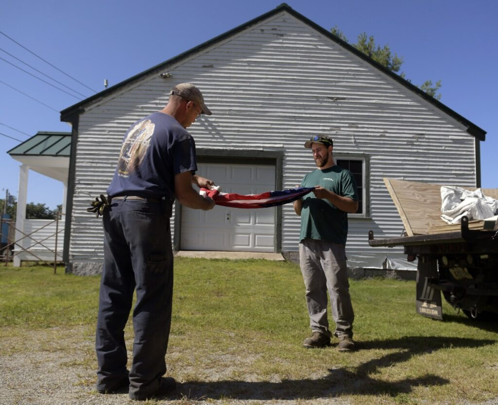 Chase Nutter, right, and Chris Dutill fold an American flag Sept. 18 that was recovered from Belgrade Town House. Nutter, a seasonal maintenance worker for the town, and Dutill, who manages the town's facilities and serves as the sexton, removed contents of the 19th-century structure ahead of restoration work.