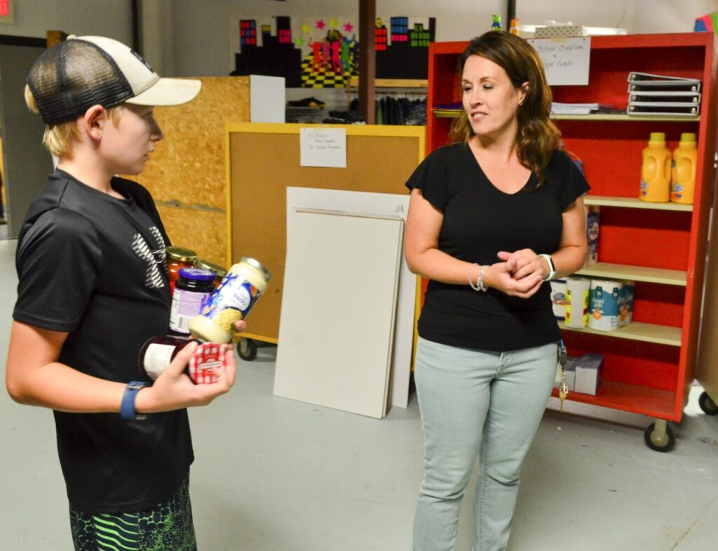 Cam Foster, left, and teacher Dixie Bonnevie talk about which shelf to put groceries as students sort food pantry donations Tuesday at Maranacook Community Middle School in Readfield.