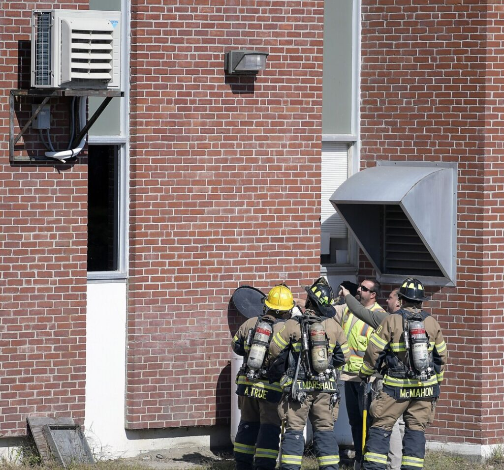 Gas technicians and Augusta firefighters inspect propane tanks Sept. 19 at the Department of Health and Human Services next to a ventilator after the building was evacuated due to a reported gas leak.