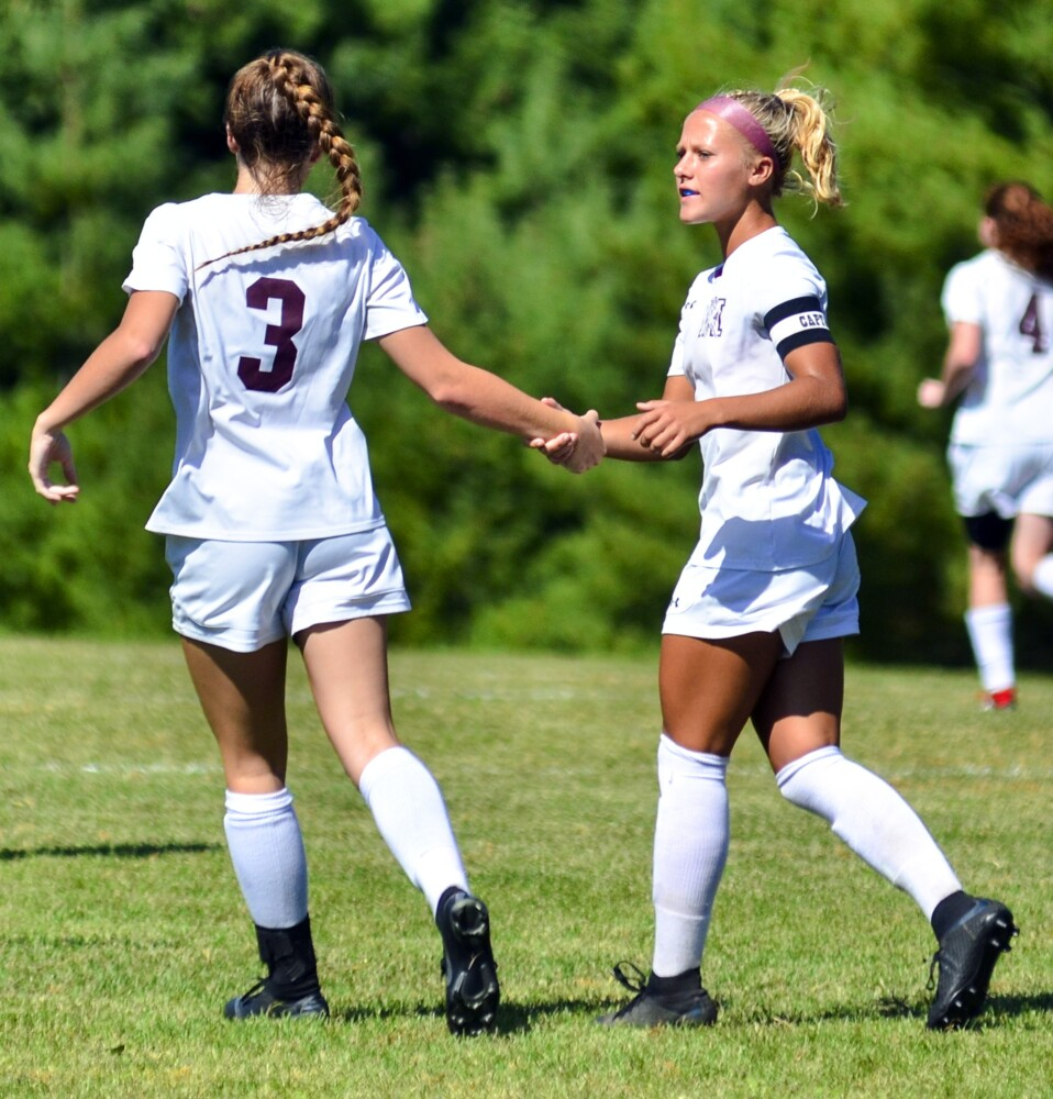 Monmouth Academy's Madisyn Smith, left, congratulates Audrey Fletcher after Fletcher scored a goal against Hall-Dale on Saturday in Farmingdale.