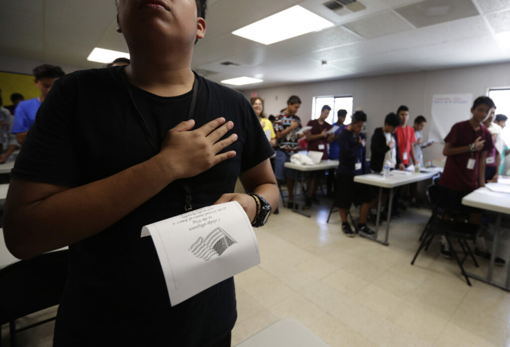 Immigrants say the Pledge of Allegiance in a writing class at a U.S. government holding center for migrant children in Carrizo Springs, Texas, in July.