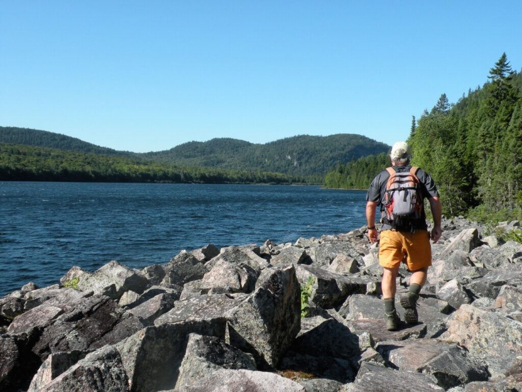 Crossing a talus field along Deboullie Pond on the Deboullie Loop Trail. The remote Deboullie Public Lands in Aroostock Country encompasses more than 20,000 acres of heavily forested country, 17 pristine ponds and a cluster of low but rugged peaks.