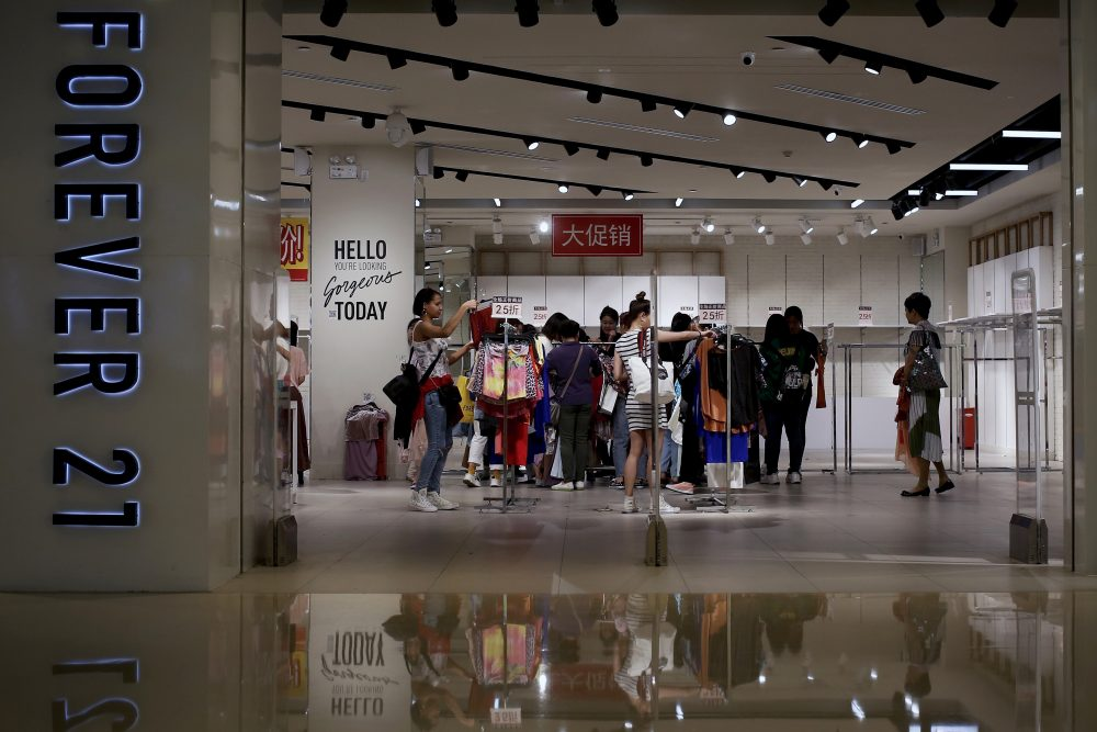 Women select clothing at a Forever 21 store in Beijing, China, last spring. The retailer announced Sunday that it has filed for Chapter 11 bankruptcy protection. Andy Wong/Associated Press