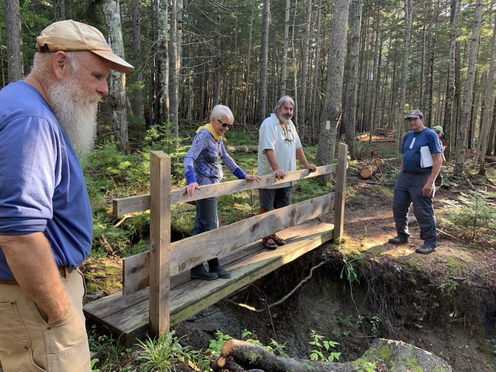 From left, recreation committee member Tom Carr, Selectman Jane Covey, Select Board Chairman Kevin Johnson and recreation committee member Tony Barrett tour the Cliff Trail, looking for hazards for those with limited mobility.
