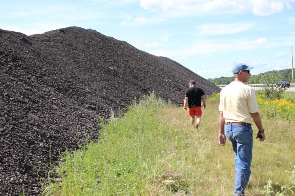 Benjamin Redmond, left, and code enforcement officer Robert Forrest inspect the growing pile of asphalt in Durham.