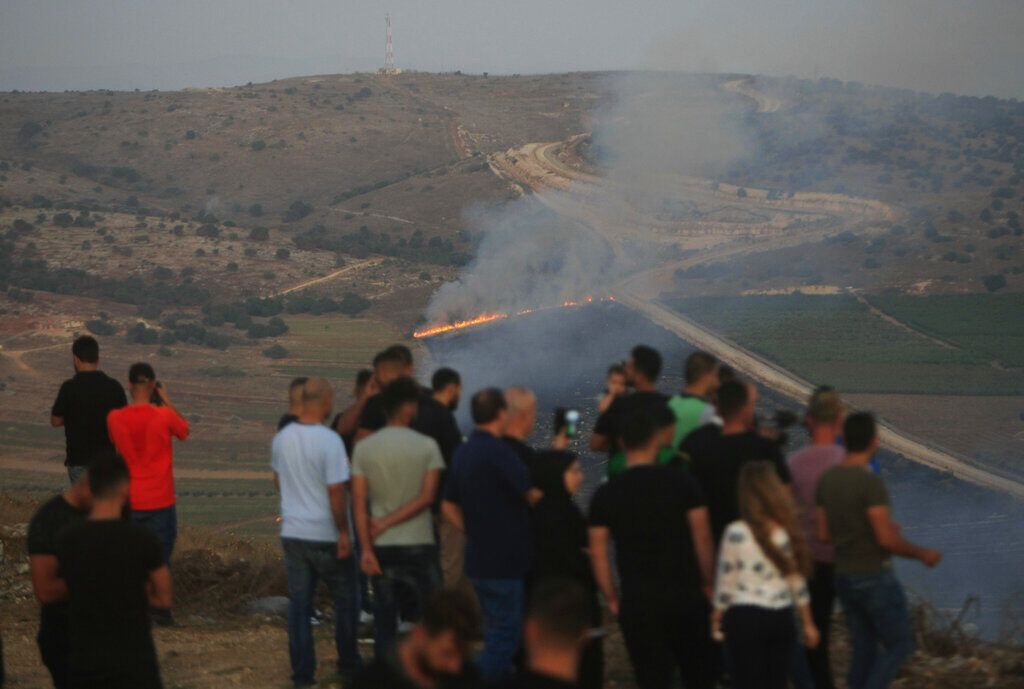 Lebanese journalists and villagers watch as Israeli army shells cause fires on the southern Lebanese border village of Maroun Al-Ras on Sunday.