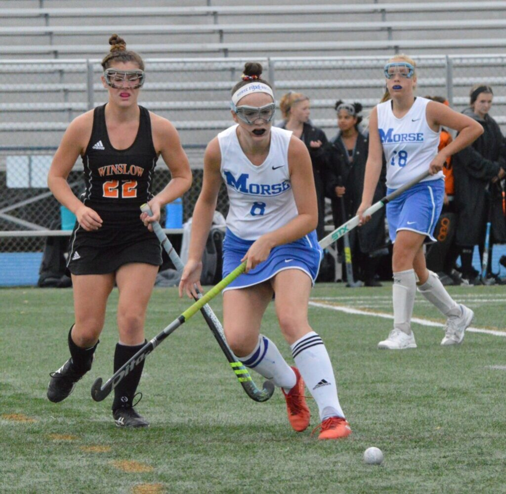 Winslow's Bodhi Littlefield, left, and Morse's Macy Coffin both eye a loose ball during the first half of Monday's field hockey game at McMann Field in Bath.