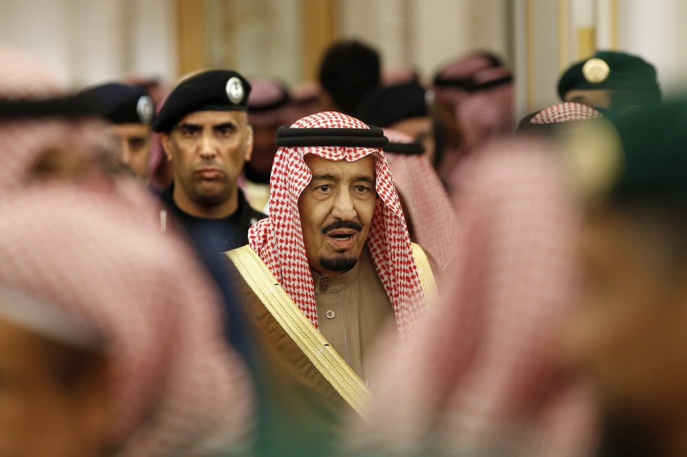 Saudi Arabia's King Salman is guarded by his bodyguard Maj. Gen. Abdulaziz al-Fagham, background, as he attends a ceremony at the Diwan royal palace in Riyadh, Saudi Arabia. Al-Fagham, a prominent bodyguard to King Salman was shot and killed in the Red Sea city of Jiddah, in what authorities described as a personal dispute, state TV reported Sunday.
