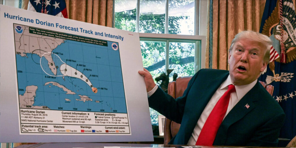 "Trump displays a modified National Hurricane Center ""cone of uncertainty"" forecast  graphic which was  altered with a marker to indicate a risk that the storm would move into Alabama from Florida."