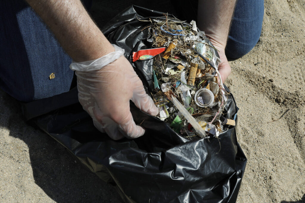 Nathan Goldberg, outreach affiliate with Alliance for the Great Lakes, holds a bag with garbage that was collected during a cleanup event in Chicago on August 22. In July, Illinois Gov. J.B. Pritzker signed into law a bill directing the state Environmental Protection Agency to examine the role of microplastics in drinking water.