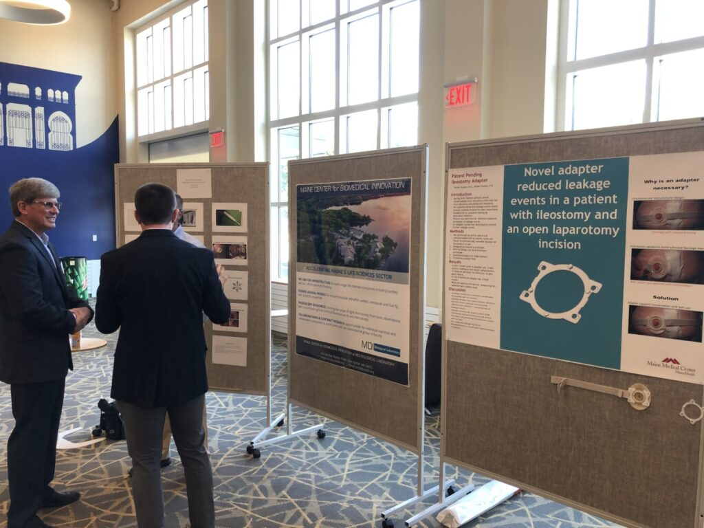 Attendees at the Maine Center for Entrepreneurs Life Science Ventures Seminar on Friday in Portland chat while standing next to a series of informational posters. The seminar's purpose was to discuss ways to grow Maine's biosciences industry.