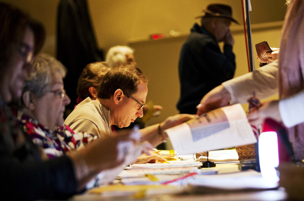 Election officials assist voters lining up to cast their ballots at a polling site for the New Hampshire primary in 2016 in Nashua, N.H.