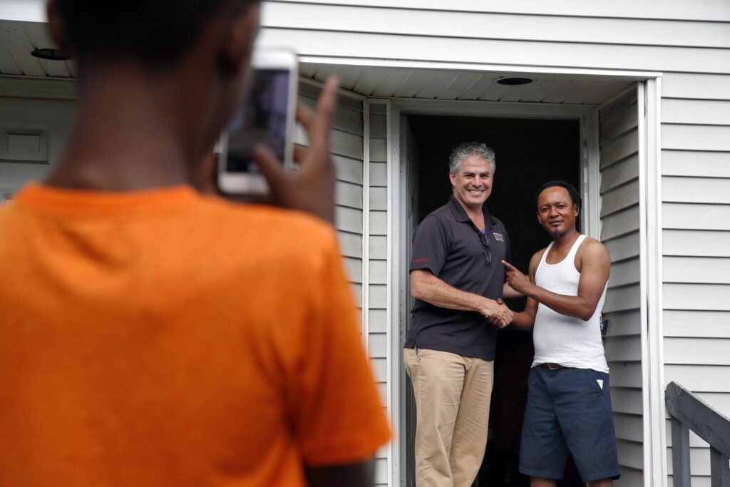 Michel Butera poses with Portland Mayor Ethan Strimling as Butera's 11-year-old son takes their photo. The men met while Strimling campaigned door-to-door last month at the Munjoy South housing development.