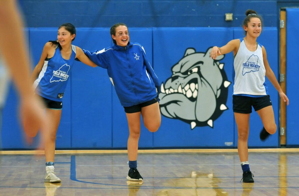 Lawrence field hockey players, from left, Holly Bolduc, and MaKenzie and Hope Bouchard, stretch at the start of practice Monday in Fairfield.