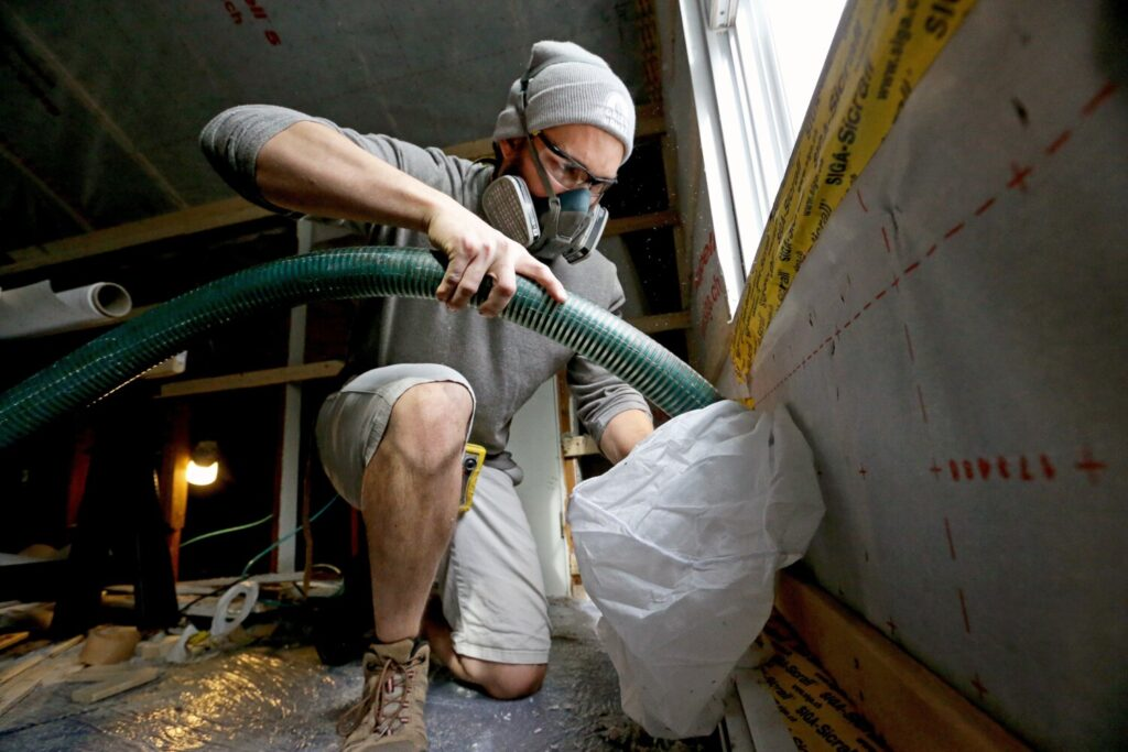 Cody Moreau, a worker from Horizon Homes, uses a hose to blow fill bays encased in a membrane with insulation in an attic in South Portland in this file photo from 2019. An updated statewide energy code for new homes and commercial buildings in Maine takes effect July 1.