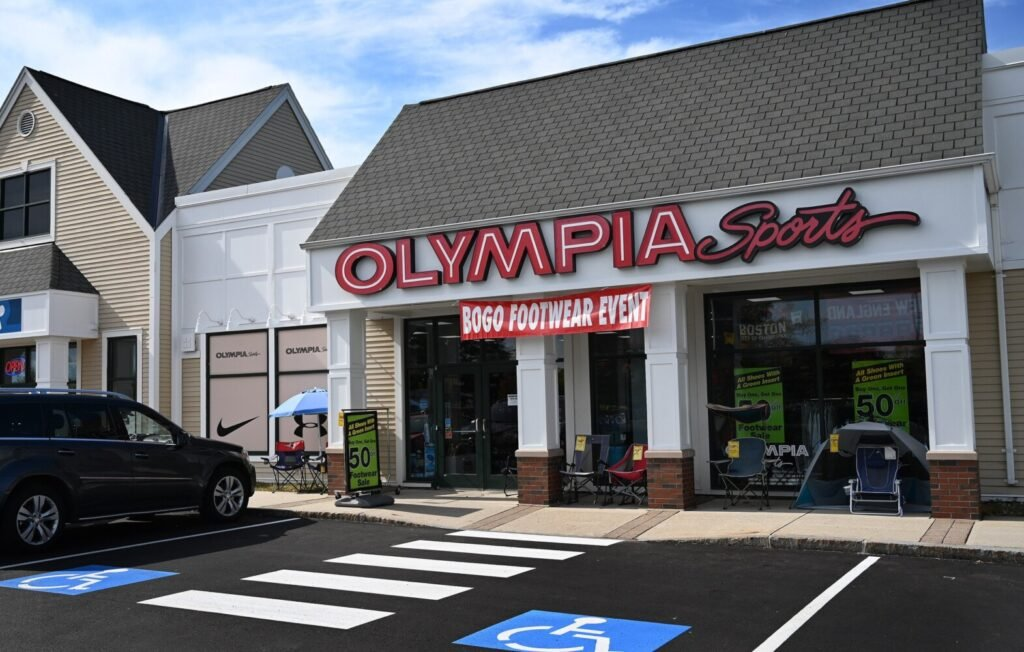 Olympia Sports in Falmouth displays sale signs in its windows Wednesday. The regional sports chain was bought by JackRabbit, a retailer backed by a California private investment firm, on Tuesday.