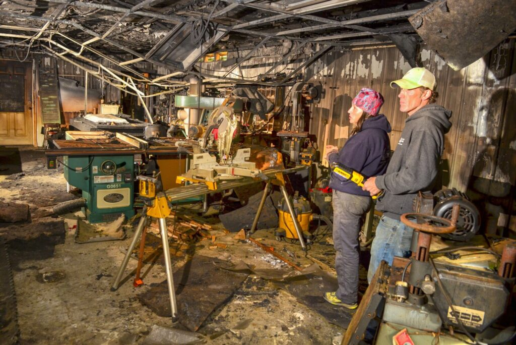 Amy Grant-Trefethen, left, and Brett Trefethen answer questions during a tour Thursday at the fire-damaged Barn Boards and More workshop in Mount Vernon.