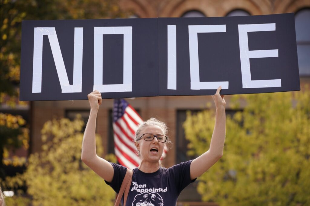 "Emily Qualey of Portland holds a ""No ICE"" sign while chanting at a protest on Monday against an Immigration and Customs Enforcement office that will soon open at One City Center in Portland."