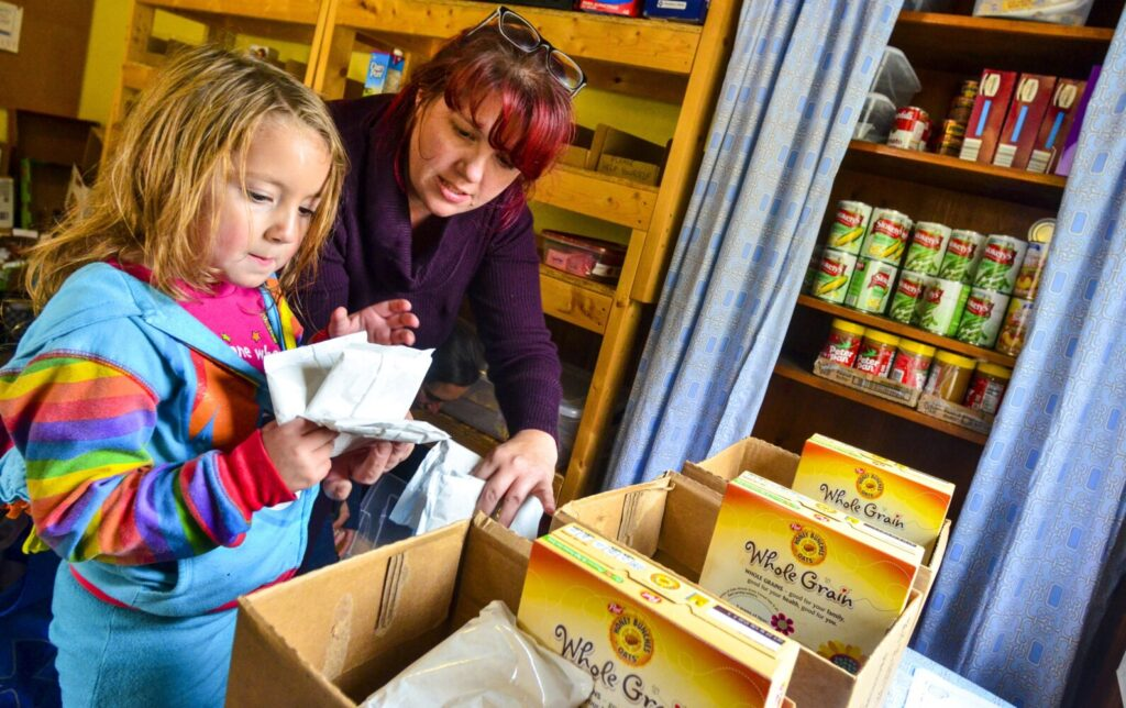 Harmony Rose Patterson, left, and her mother Amber Patterson pack food for the lunch box program Oct. 17 at the Fayette Baptist Church Food Pantry in Fayette. The lunch box program packs boxes for Fayette Elementary School students and has small section of shelves in the pantry.