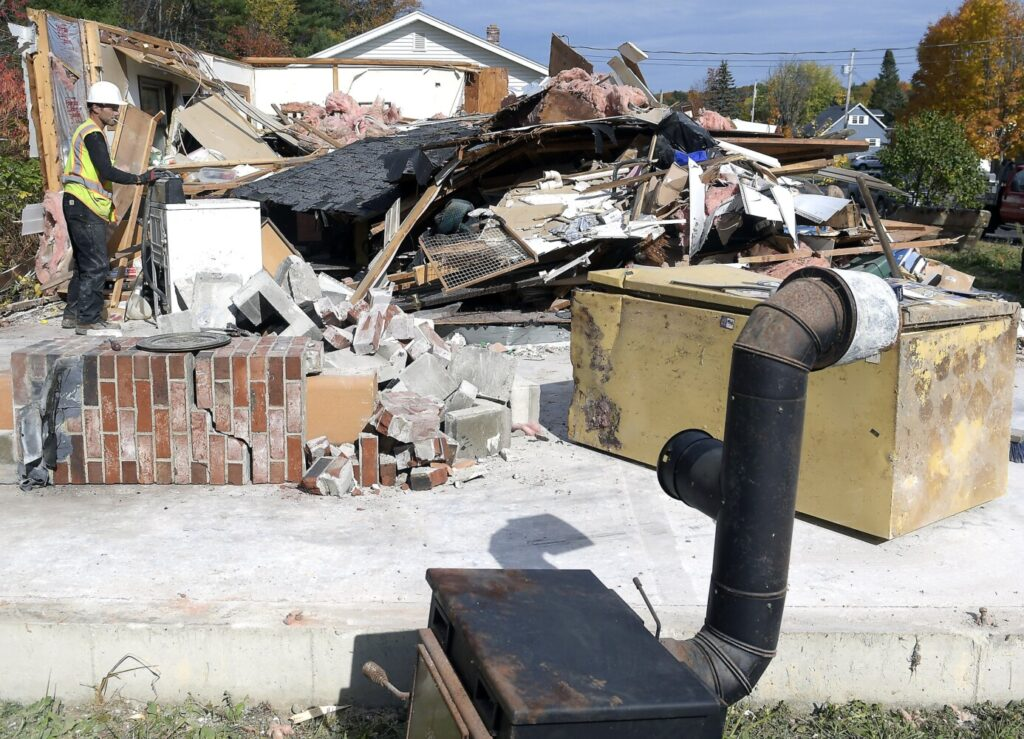 A worker razes the home at 68 Windy St. Tuesday in Augusta.
