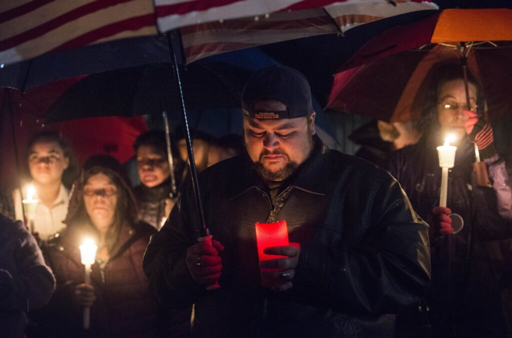 Dustin Thibodeau, a neighbor of Melissa Sousa, cries during a candlelight vigil Sunday night outside Sousa's apartment on Gold Street in Waterville.
