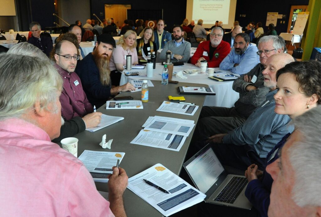 Seth Hall of S and J Llama, LLC, back to camera, leads a discussion during the small group portion of the Maine Broadband Summit at Thomas College in Waterville Monday.