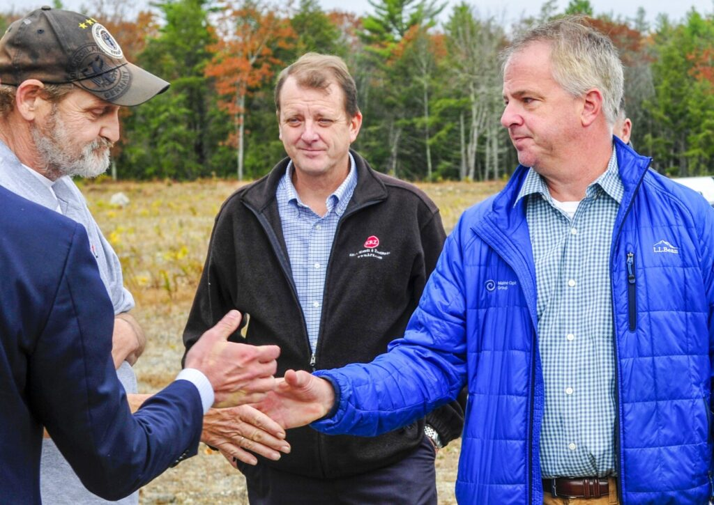 Bill Lovely, left, shakes hands with Shawn Lyden, of Maine Capital Group, after Lyden's high bid won the auction Oct. 30 in Gardiner.